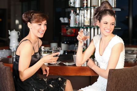 Two beautiful young women with great smile and hairstyle sitting at a bar, drinking water. Stock Photo - 6392666