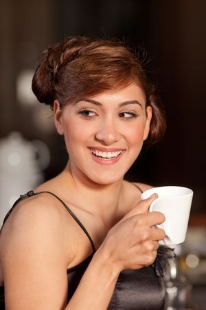 Beautiful young women with great smile and hairstyle sitting at a bar, drinking coffee. Stock Photo - 6392670