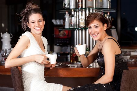 Two beautiful young women with great smile and hairstyle sitting at a bar, drinking coffee. Stock Photo