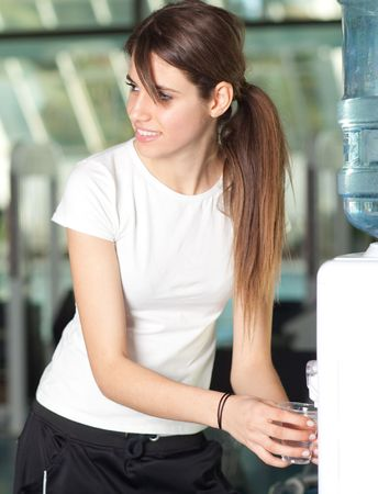 Happy young woman drinking water in the gym smiling