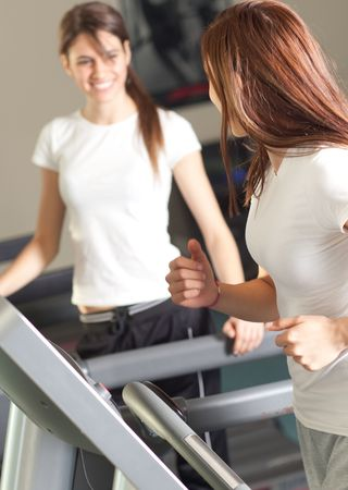 Happy young women on a treadmill in the gym smiling photo