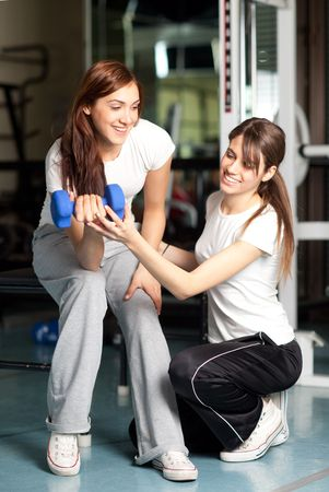 Young woman and female instructor in the gym doing bicep curl with blue dumbbell photo