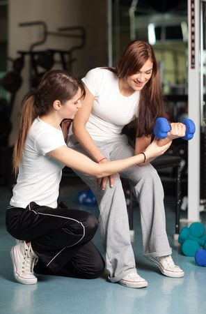 Young woman and female instructor in the gym doing bicep curl with dumbbell photo
