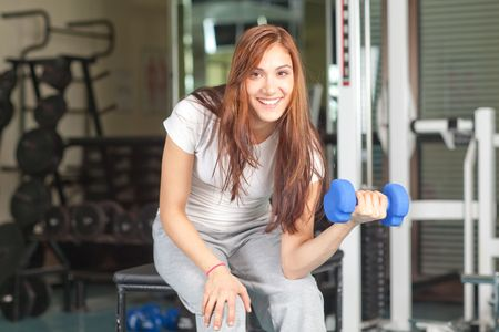 Happy young women doing bicep curl in the gym smiling to the camera photo