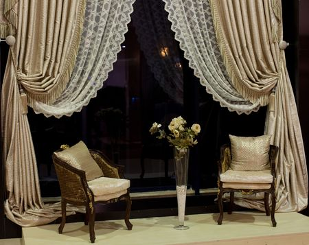 tassels: Luxurious old-fashioned chairs, vase with yellow roses and designer window curtains