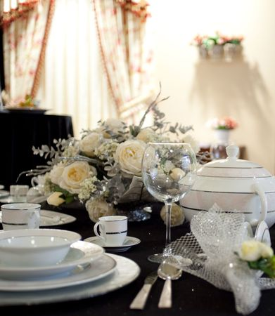 Elegant table in restaurant in white and yellow and black, selective focus on glass.