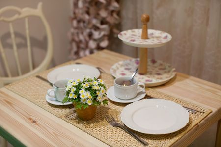 restauration: Beautiful rustic-style wooden table, white porcelain, bunch of margaritas in pot; selective focus on flowers.