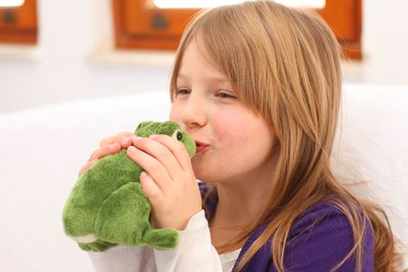 Young girl with blonde hair and purple dress sitting on sofa kissing a toy frog, selective focus on lips photo