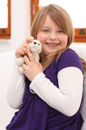 Young girl with blonde hair and purple dress sitting on sofa with teddy bear in hand, smiling to the camera. photo