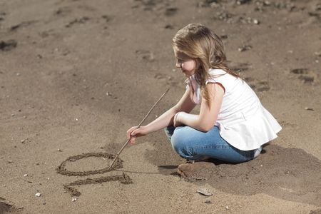 Blonde young girl on the beach writing the number ten in the sand, selective focus on writing photo
