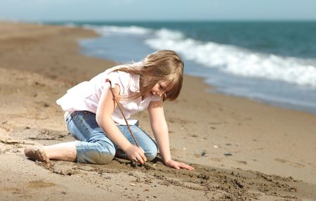 Happy blonde young girl on the beach writing in the sand