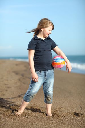 wet jeans: Happy blonde young girl with a colorful ball on the beach looking to the sea Stock Photo