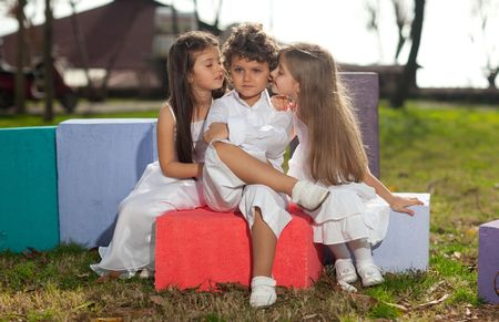Cute young boy with two beautiful young blonde girls with white dresses sitting on colorful cubes, girls kissing boy, sun reflection in hair, backlight