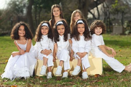 Seven happy young children including triplets with white clothes sitting on yellow cubes smiling, sun reflection in hair, backlight; shallow depth of field