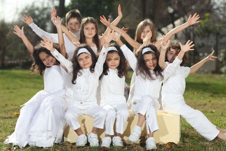 Eight happy young children including triplets with white clothes sitting on yellow cubes cheering, sun reflection in hair, backlight
