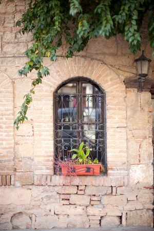 Old window and ancient wall with lamp and flowers in Turkey photo