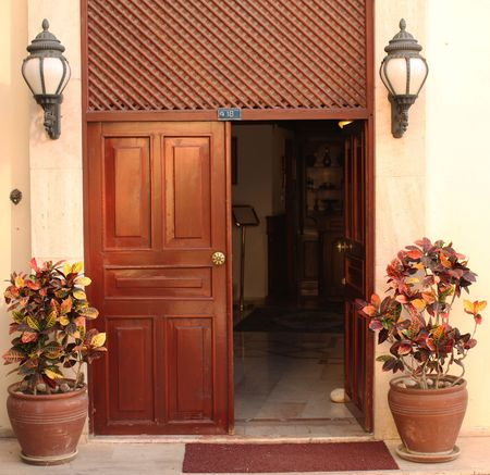 House entrance with old door, two flowerpots with colorful flowers and old-style lamps in Turkey Stock Photo