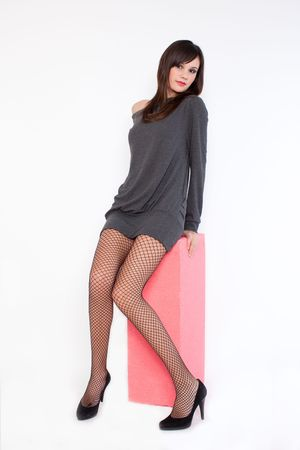 attractive young woman with high heels and fishnet stockings posing in studio on white background  photo