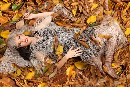 Beautiful vampire woman lying on the ground on leaves, magic wand in hand. photo