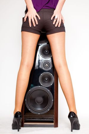 attractive young woman with sexy pants, long legs and high heels standing in front of a loudspeaker, hands on bottom, white background