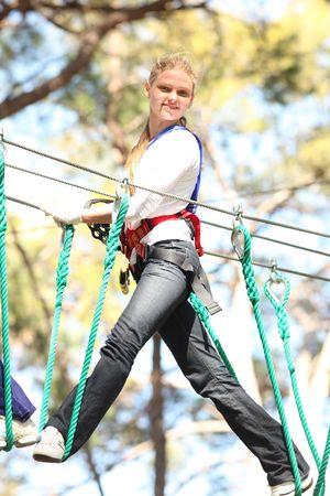 roped: Joven y bella mujer rubia escalada aquellos en el Parque de aventuras