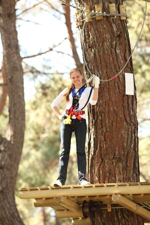 Young beautiful blonde woman climbing roped up in adventure park, smiling to the camera photo
