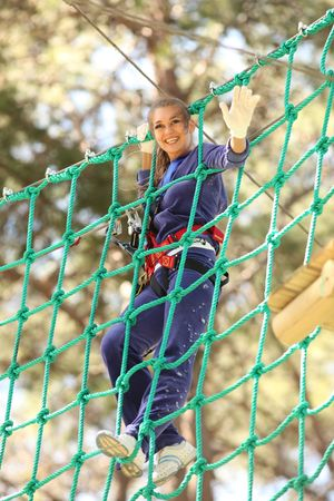 Happy young beautiful blonde woman climbing roped up in adventure park, waving hands and smiling to the camera