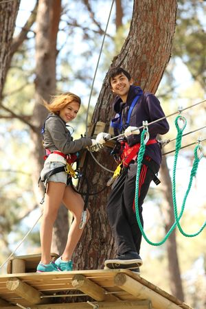 Happy young couple climbing roped up in adventure park, smiling to the camera