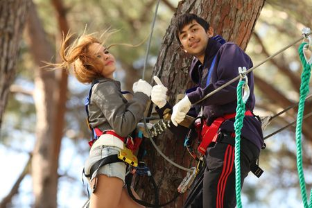 Happy young couple climbing roped up in adventure park, smiling to the camera, showing thumb up