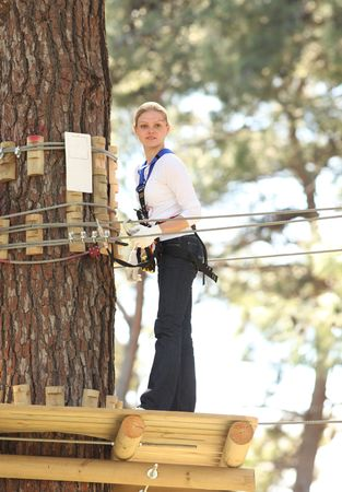 Happy young beautiful blonde woman climbing roped up in adventure park photo