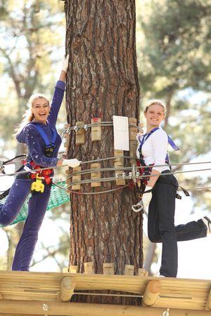 roped: Dos j�venes felices hermosas mujer rubia escalada aquellos en el Parque de aventuras, sonriendo a la c�mara