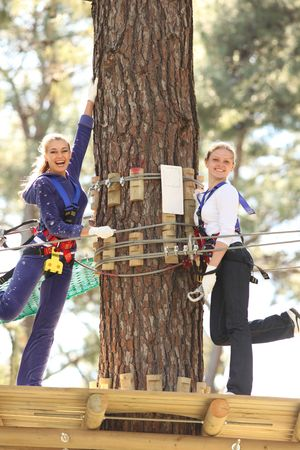 obstacle course: Two happy young beautiful blonde woman climbing roped up in adventure park, smiling to the camera