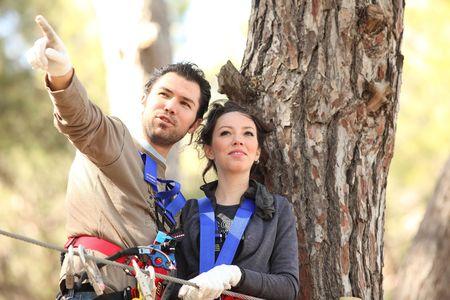 roped: Feliz pareja joven escalada aquellos en el Parque de aventuras, sonriendo  Foto de archivo