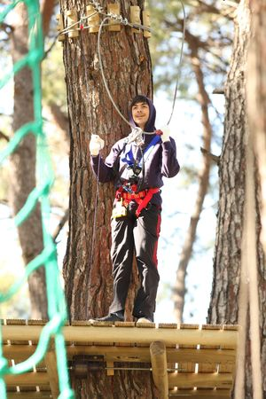 Young man climbing roped up in adventure park photo