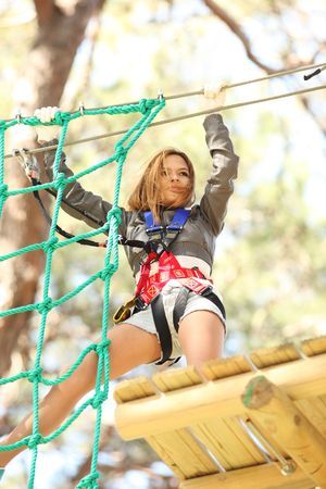 obstacle course: Young beautiful blonde woman climbing roped up in adventure park Stock Photo