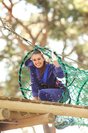 Happy young beautiful blonde woman climbing roped up in adventure park, smiling to the camera photo
