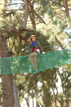 Happy young beautiful blonde woman climbing roped up in adventure park, smiling to the camera Stock Photo