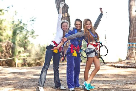 Three happy young beautiful women with harness in adventure park, smiling to the camera photo