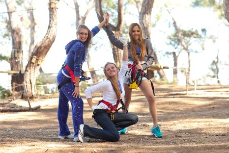 Three happy young beautiful women with harness in adventure park, smiling to the camera