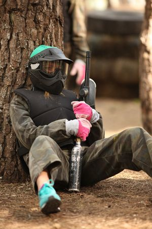 Young paintball player with helmet and gun taking a break