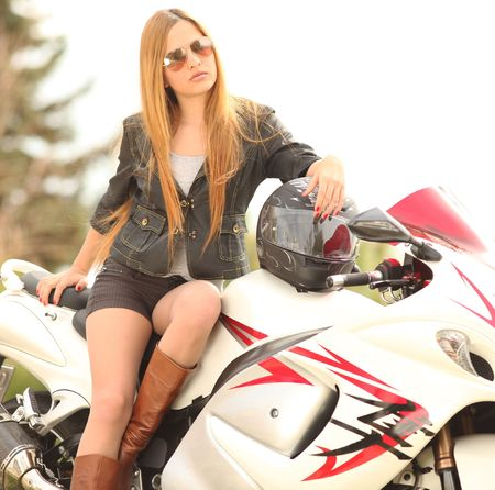 Beautiful blonde woman with sunglasses sitting on motorcycle; shallow depth of field