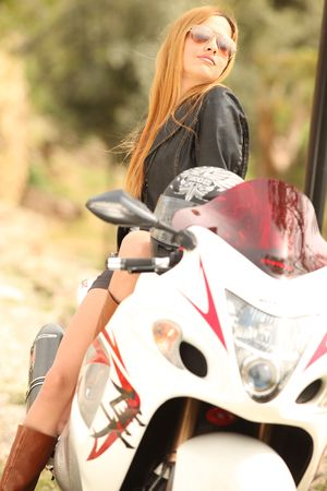 Beautiful blonde woman with sunglasses sitting on motorcycle; shallow depth of field photo
