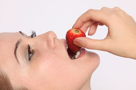 Close up of beautiful young woman eating strawberry photo