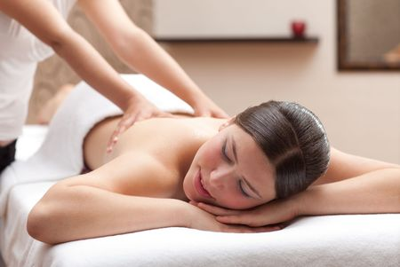 Beautiful young woman receiving back massage in spa, shallow depth of field, focus on face