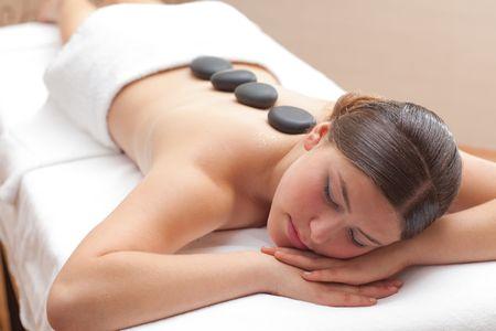masajes relajacion: Joven y bella mujer goza de un tratamiento de piedra mineral caliente en spa, la profundidad de campo, centrarse en la cara