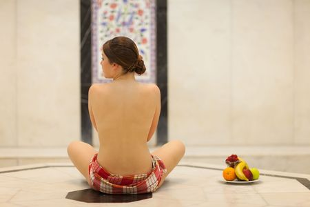Beautiful young topless woman in turkish bath (Hammam) with fruit plate Stock Photo