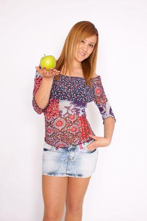 Jeune belle femme blonde avec une pomme verte sur fond blanc, souriant à la caméra, faible profondeur de champ, se concentrer sur le visage