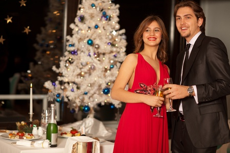 Happy young couple with champagne glasses in hand at christmas, beautiful table and tree in the background, shallow depth of field. Stock Photo