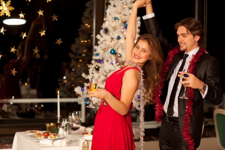 Happy young couple with champagne glasses in hand dancing at christmas, beautiful table and tree in the background, selective focus on girl.