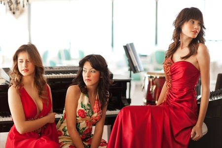 Three beautiful young women with long dresses sitting at a piano, shallow depth of field, focus on middle girl photo